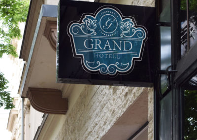 Mockup av Grand hotell sin logo på ett skilt