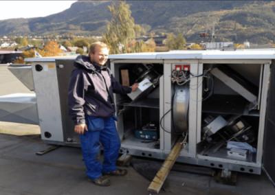 En arbeider ved Klima og Energiteknitt som undersøker en installasjon
