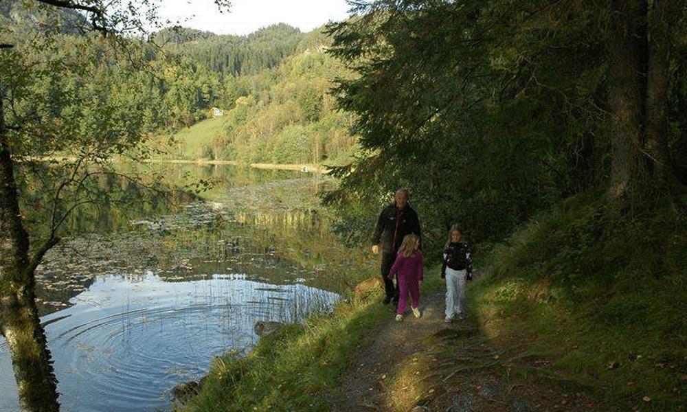 En mann og to jenter på tur rundt Rødstjødnå