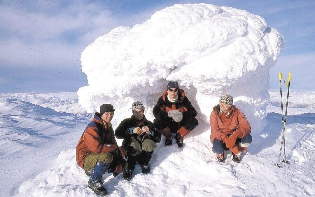 4 personer som sitter på huk under en haug med snø på Kyrkjenuten