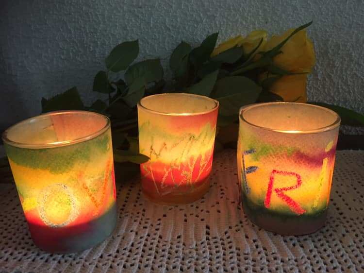 3 lys i fargerike kopper med noen gule roser bak