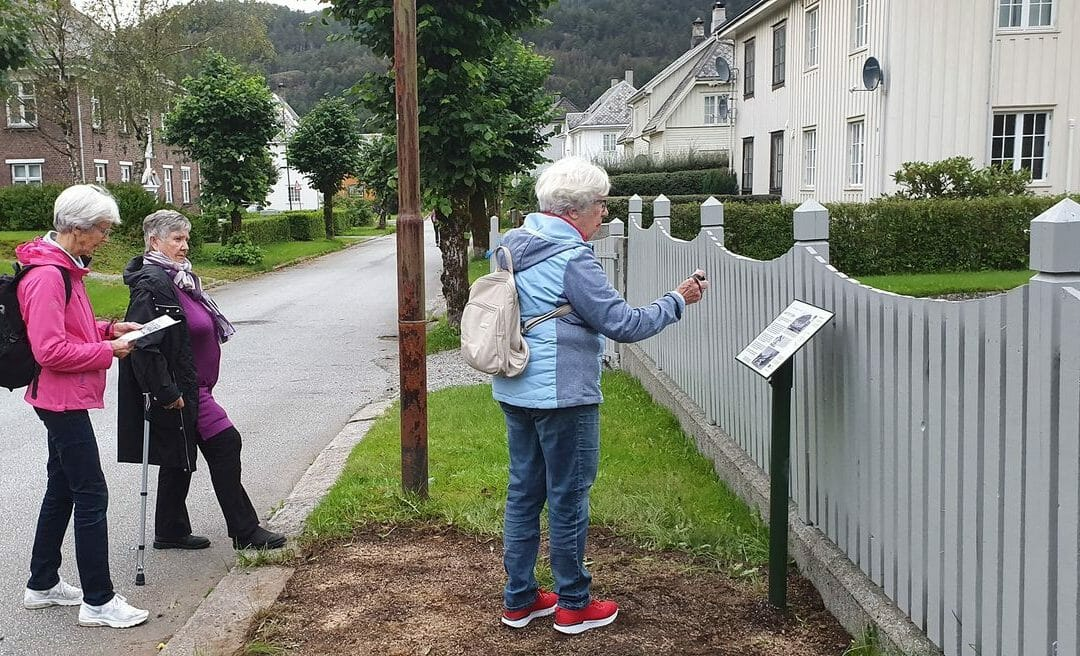 Tre gamle damer som leser historie fra ett skilt i Åbøbyen